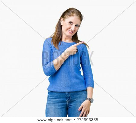 Beautiful middle age mature woman wearing winter sweater over isolated background cheerful with a smile of face pointing with hand and finger up to the side with happy and natural expression on face