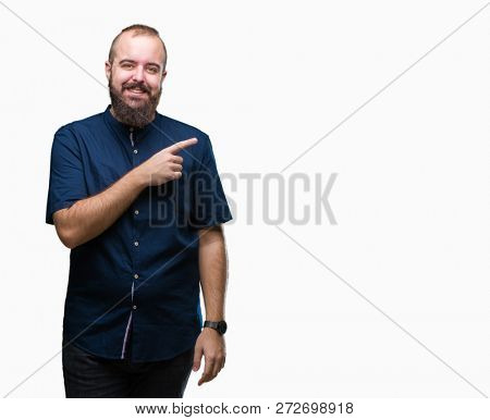 Young caucasian hipster man over isolated background cheerful with a smile of face pointing with hand and finger up to the side with happy and natural expression on face looking at the camera.