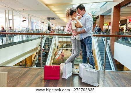 Couple in love in the shopping center with many shopping bags flirting