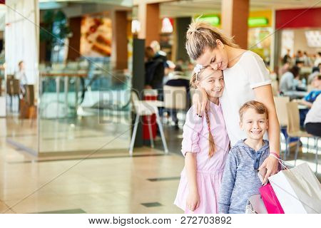 Happy mother and kids shopping with shopping bags in shopping mall