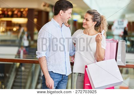 Couple shopping with credit card and shopping bags in shopping mall