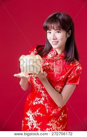 Beauty Woman Wear Cheongsam And Show Golden Piggy Bank In Chinese New Year