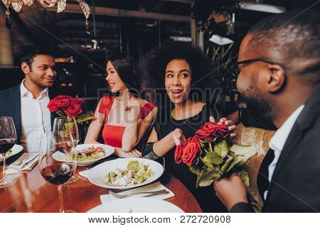 Friends In A Restaurant Enjoying Romantic Evening. Group Happy Friends Enjoying Dating In Restaurant