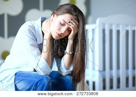 Young Tired Woman Sitting On The Bed Near Childrens Cot. Young Mom.
