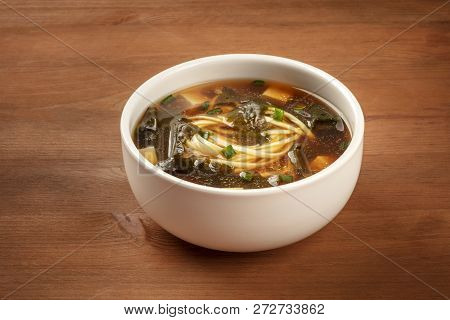 A Photo Of A Bowl Of Miso Soup With Tofu, Scallions, Noodles, And Wakame Seaweed, On A Dark Wooden B