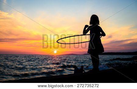 Girl Is Watching Amazing Sea Sunset With Hula Hoop.