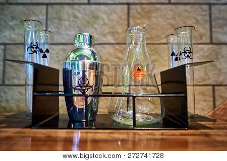 Shaker, Flask And Test Tubes With The Symbol Of Biological Hazard, Flammable Liquid And Radiation On
