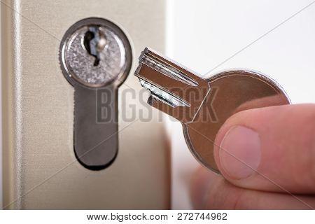 Close-up Of A Man Holding Broken Key Near Keyhole