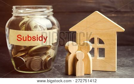 The Family Is Standing Near A Glass Jar With The Inscription Subsidy. Financial Aid, Support To The