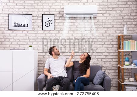 Happy Young Couple Sitting On Sofa Operating Air Conditioner At Home