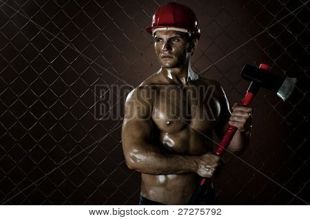 poster of the beauty muscular worker chopper man in safety helmet with big heavy ax in hands tired appearance on netting fence background