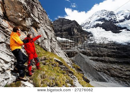 Alpinists pointing a mountain route on Monch Peak (4107m), Berner Oberland, Switzerland