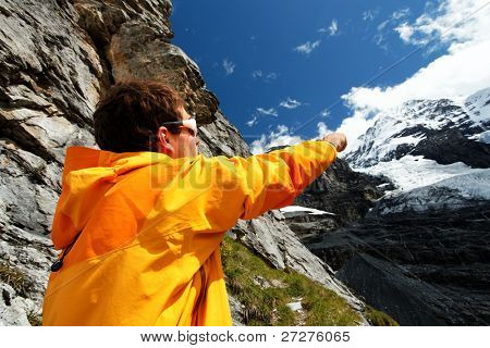 Alpinist pointing a mountain route on Monch Peak (4107m), Berner Oberland, Switzerland