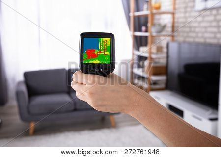 Woman Using Infrared Thermal Camera In Living Room