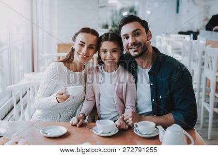 Family Resting In Cafe. Family Is A Mother, Father, Daughter And Son. People Is Drinking A Tea From