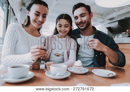 Family Resting In Cafe. Family Is A Mother, Father, Daughter And Son. People Is Eating Cakes And Dri