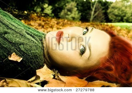 beautiful fashion model lying in the leaves