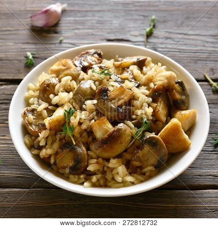 Bowl Of Risotto With Mushrooms And Pieces Of Chicken Meat On Wooden Table.