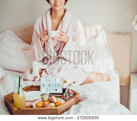 Good Morning Concept. Croped Woman In Bathrobe Sitting On The Bed, Drinking Coffee And Has Her Break