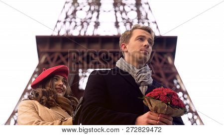 Woman looking at beloved man with bouquet with embarrassment, late for date, stock footage poster