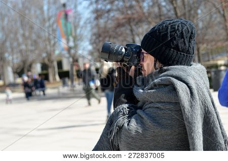 Woman Holding A Camera And Photographing In A Public Place In The City Of Chicago