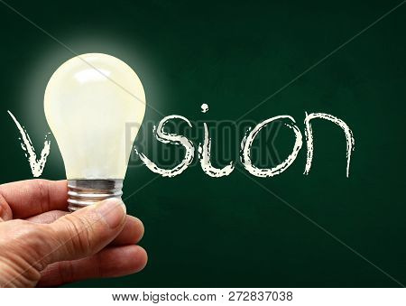 Man Holding Illuminated Bulb With Bare Hands Against Chalkboard With The Word Vision. Concept Of Bri