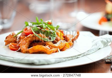Penne Pasta In Tomato Sauce With Chicken, Parsley In Pan. Chicken Italian Penne Pasta Over Black Bac