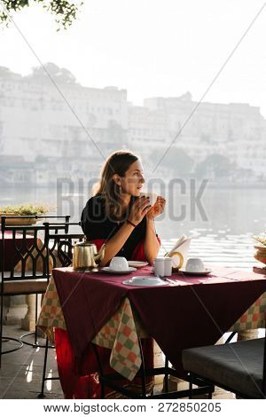 Western woman having a teatime at a cafe in Udaipur poster