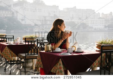 Western woman having a teatime at a cafe in Udaipur