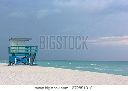 Lifeguard Cabin On Empty Miami Beach At Cloudy Sunrise. Seagulls On A Sandy Sea Beach And Lonely Cab
