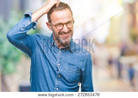 Middle age hoary senior man wearing glasses over isolated background confuse and wonder about question. Uncertain with doubt, thinking with hand on head. Pensive concept.