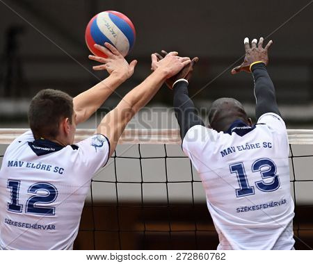 KAPOSVAR, HUNGARY – NOVEMBER 29, 2018: Norbert Kholmann (white 12) in action at a Hungarian National Cup volleyball game between Kaposvar (blue) and MAV Elore (white) in Sportcsarnok Kaposvar.