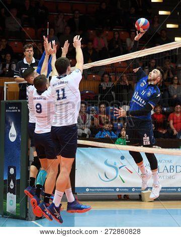 KAPOSVAR, HUNGARY – NOVEMBER 29, 2018: Gabor Bogoly (with ball) in action at a Hungarian National Cup volleyball game between Kaposvar (blue) and MAV Elore (white) in Sportcsarnok Kaposvar.
