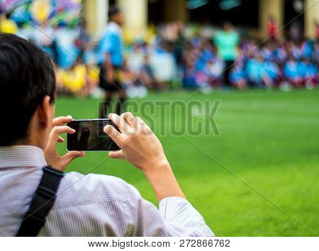 Man In Work Uniform Watch And Shoot Football Competitions Beside Football Field