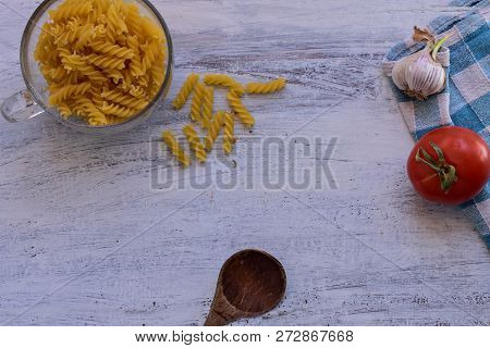 Uncooked Pasta Whit Fresh Garlic And Red Tomato At Light Wooden Background/ Flatware/ Food Backgroun
