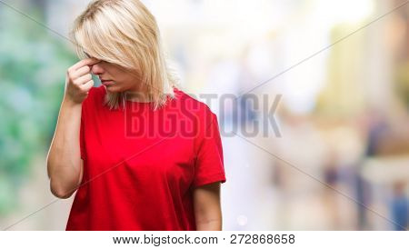 Young beautiful blonde woman wearing red t-shirt over isolated background tired rubbing nose and eyes feeling fatigue and headache. Stress and frustration concept.