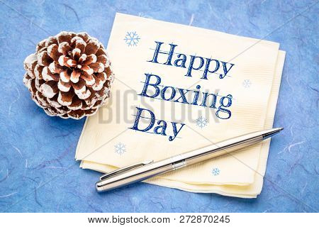 Happy Boxing Day -  handwriting on a napkin with a frosty pine cone
