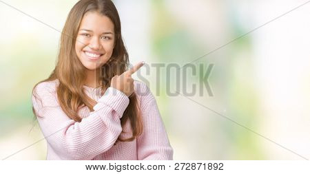 Young beautiful brunette woman wearing pink winter sweater over isolated background cheerful with a smile of face pointing with hand and finger up to the side with happy and natural expression on face