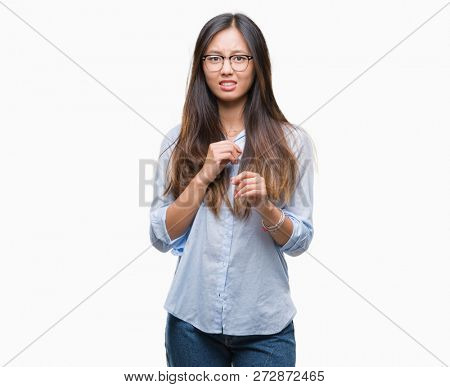 Young asian business woman wearing glasses over isolated background disgusted expression, displeased and fearful doing disgust face because aversion reaction. With hands raised. Annoying concept.