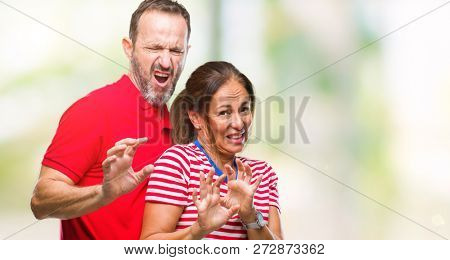 Middle age hispanic couple in love over isolated background disgusted expression, displeased and fearful doing disgust face because aversion reaction. With hands raised. Annoying concept.