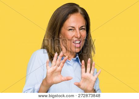 Beautiful middle age business adult woman over isolated background disgusted expression, displeased and fearful doing disgust face because aversion reaction. With hands raised. Annoying concept.