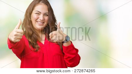 Beautiful plus size young business woman over isolated background approving doing positive gesture with hand, thumbs up smiling and happy for success. Looking at the camera, winner gesture.