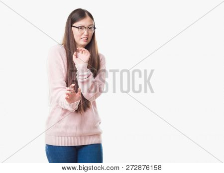 Young Chinese woman over isolated background wearing glasses disgusted expression, displeased and fearful doing disgust face because aversion reaction. With hands raised. Annoying concept.
