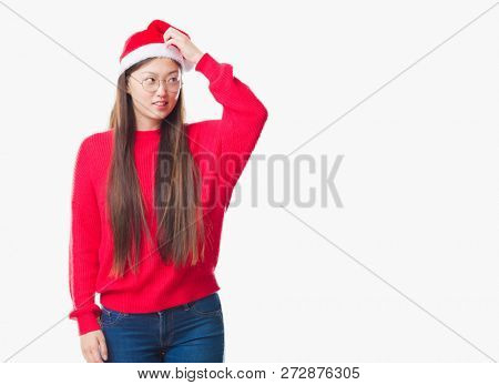 Young Chinese woman over isolated background wearing christmas hat confuse and wonder about question. Uncertain with doubt, thinking with hand on head. Pensive concept.