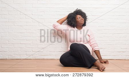Young african american woman sitting on the floor at home confuse and wonder about question. Uncertain with doubt, thinking with hand on head. Pensive concept.