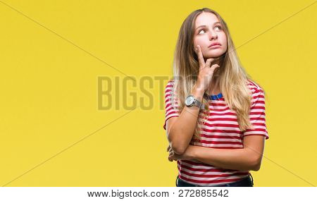 Young beautiful blonde woman over isolated background with hand on chin thinking about question, pensive expression. Smiling with thoughtful face. Doubt concept.