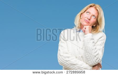 Middle age blonde woman wearing winter sweater over isolated background with hand on chin thinking about question, pensive expression. Smiling with thoughtful face. Doubt concept.