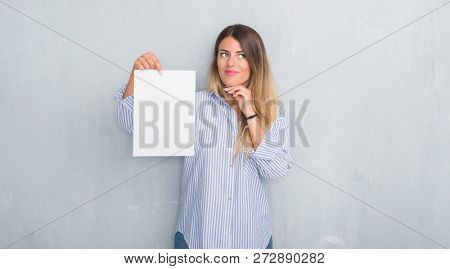 Young adult woman over grey grunge wall holding blank paper sheet serious face thinking about question, very confused idea