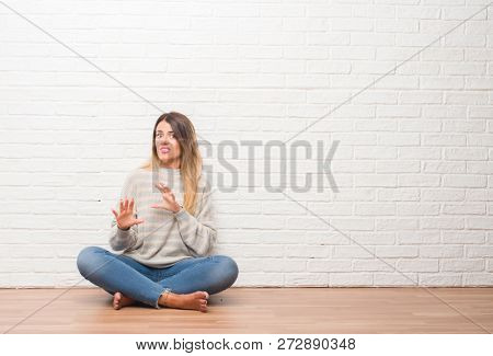 Young adult woman sitting on the floor over white brick wall at home disgusted expression, displeased and fearful doing disgust face because aversion reaction. With hands raised. Annoying concept.