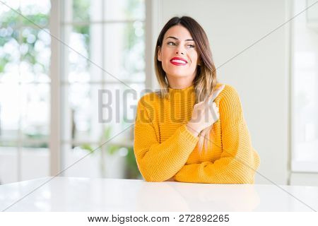 Young beautiful woman wearing winter sweater at home cheerful with a smile of face pointing with hand and finger up to the side with happy and natural expression on face